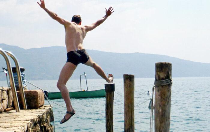 Mann springt ins Wasser und breitet die Arme aus / IMPULSE Sei Frech